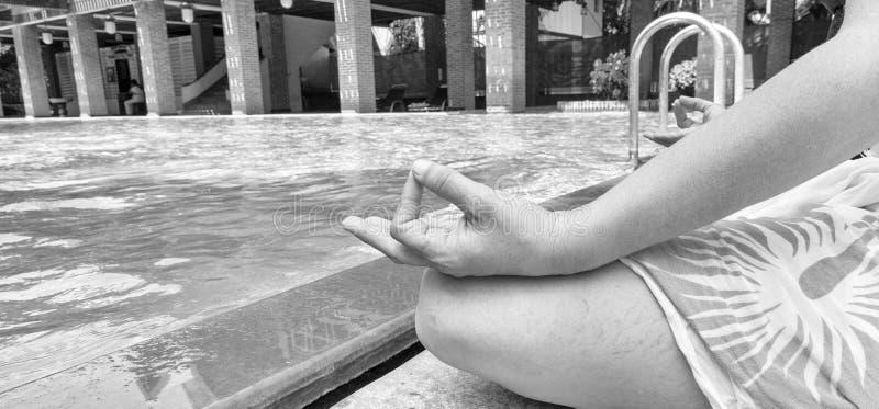 la mujer joven 40 que medita el agua azulverde tranquila de desatención, se cierra encima de la vista de sus manos y cruzó las pi fotos de archivo