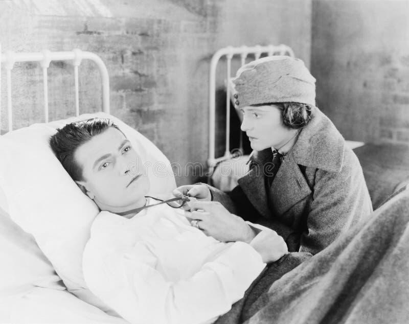 La mujer joven que mira un bloqueado de un hombre joven que esté mintiendo en la cama en un hospital (todas las personas represen imagenes de archivo