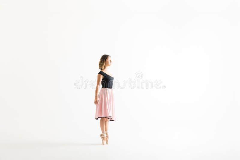 La mujer joven que practica su ballet se mueve en el fondo blanco imagen de archivo