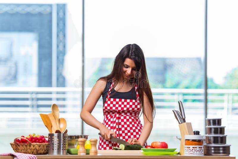 La mujer joven que prepara la ensalada en la cocina foto de archivo