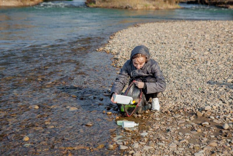 La mujer joven que recoge basura pl?stica de la playa y que la pone en las bolsas de pl?stico negras para recicla Limpieza y reci fotografía de archivo libre de regalías