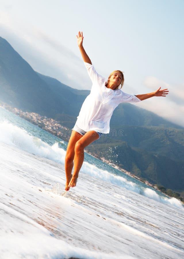 La mujer joven que saltaba con las manos aumentó en la playa imagenes de archivo