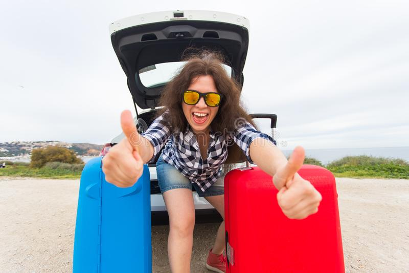 La mujer joven que se coloca cerca apoya del coche que muestra los pulgares para arriba y que consigue listo para ir Viaje por ca fotos de archivo