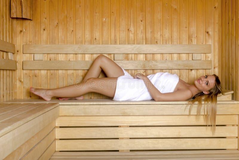 La mujer joven que se relaja en sauna y goza del aire caliente imágenes de archivo libres de regalías