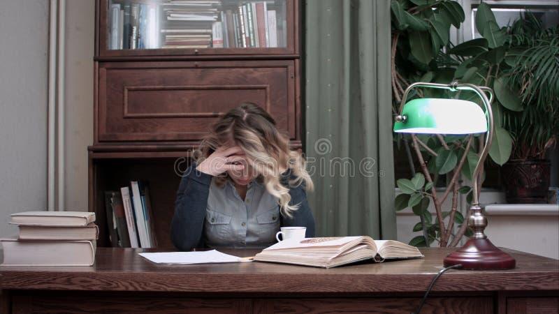 La mujer joven que se sentaba en el escritorio cansó de trabajar y de tomar su cabeza en manos foto de archivo