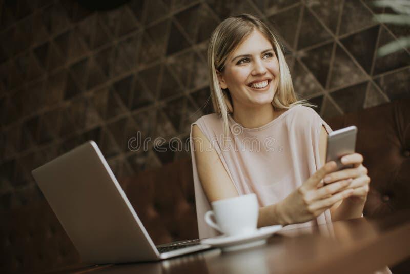La mujer joven que se sienta en café, el café de consumición y practican surf al interno fotos de archivo libres de regalías