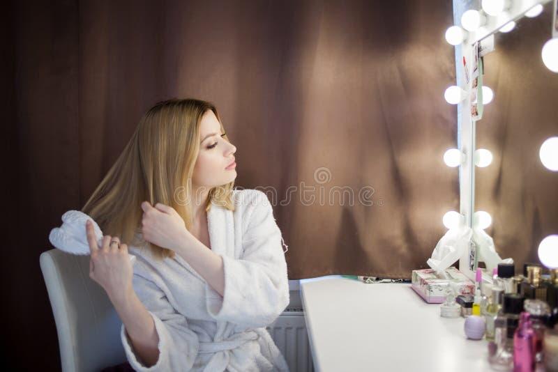 La mujer joven que sorprende cepilla su pelo delante del espejo Retrato de la muchacha hermosa fotografía de archivo libre de regalías