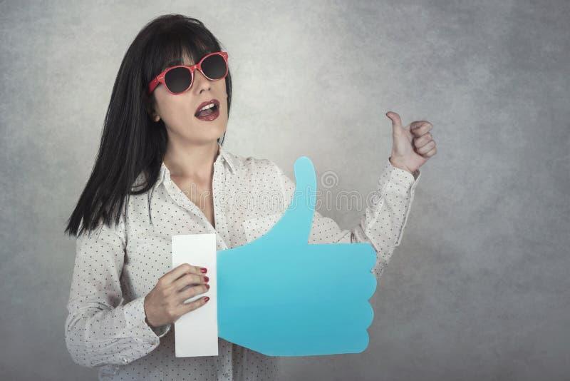 La mujer joven que sostiene a le gusta el icono fotografía de archivo libre de regalías
