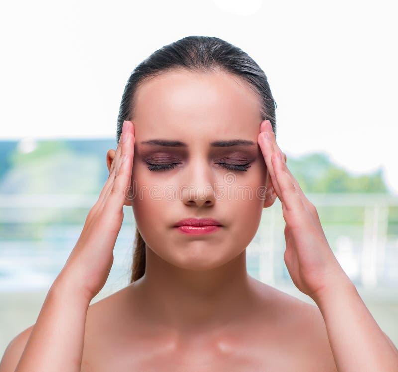 La mujer joven que sostiene sus templos con dolor de cabeza imagen de archivo