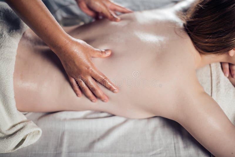La mujer joven que tomaba placer en cama del masaje, con los ojos se cerró Mujer Salón del balneario fotografía de archivo libre de regalías