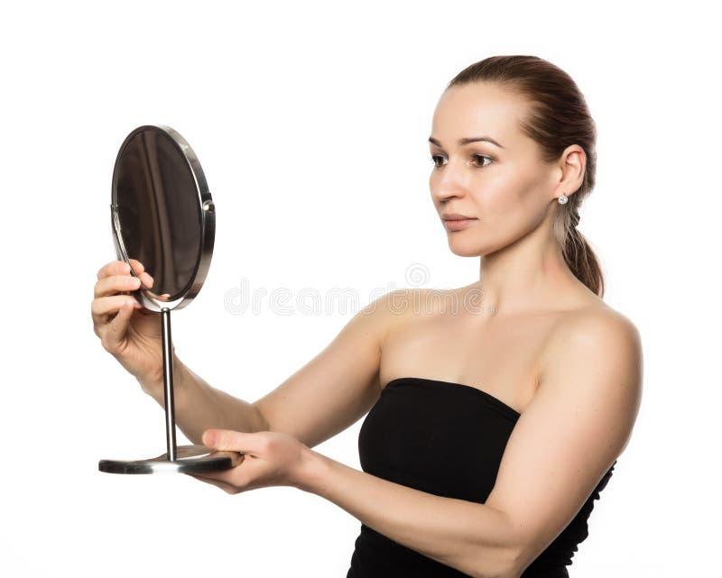 La mujer joven realiza ejercicios antienvejecedores aptitud de la cara La muchacha mira en el espejo imagen de archivo