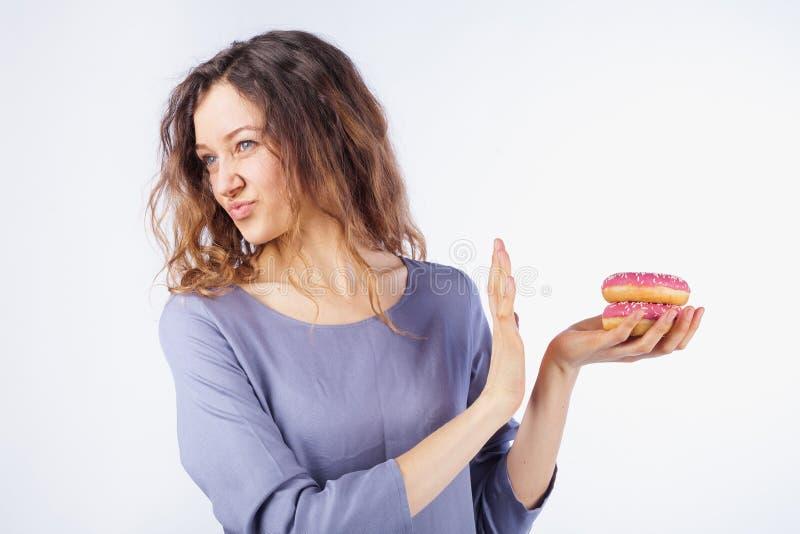 La mujer joven rechaza los anillos de espuma dañinos El concepto de dieta y de consumición sana fotografía de archivo libre de regalías