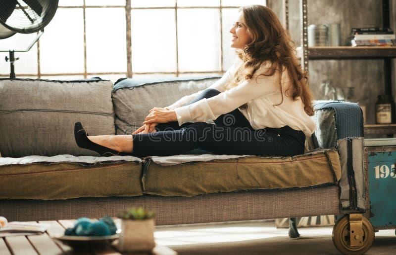 La mujer joven relajada sonriente es relajante en el sofá imagen de archivo