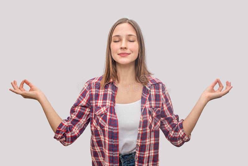 La mujer joven relajada y agradable mantiene etes cerrados y lleva a cabo las manos en actitud concentrada Ella está haciendo yog fotos de archivo libres de regalías
