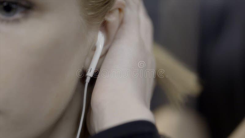 La mujer joven remete el pelo detrás del oído acci?n La mujer joven atractiva remete su pelo detrás de su oído con el auricular m imagen de archivo libre de regalías