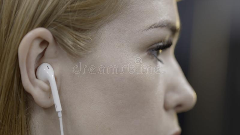 La mujer joven remete el pelo detrás del oído acci?n La mujer joven atractiva remete su pelo detrás de su oído con el auricular m foto de archivo