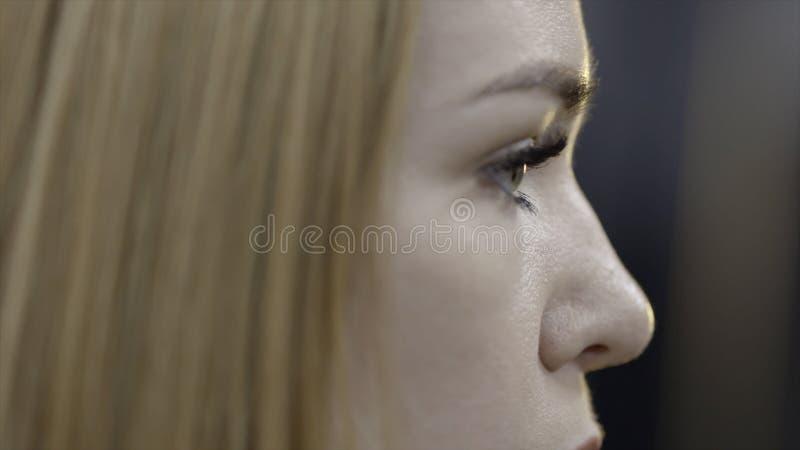 La mujer joven remete el pelo detrás del oído acci?n La mujer joven atractiva remete su pelo detrás de su oído con el auricular m imágenes de archivo libres de regalías