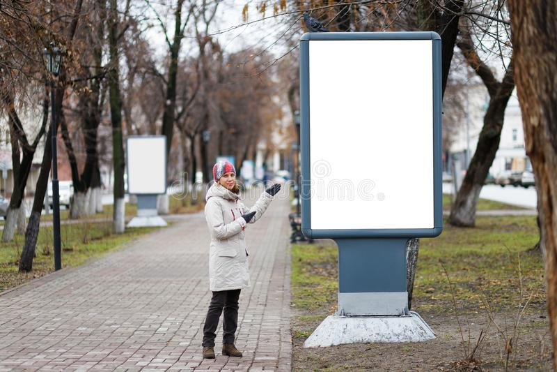 La mujer joven señala a una cartelera vacía en el callejón en el parque de la ciudad fotografía de archivo
