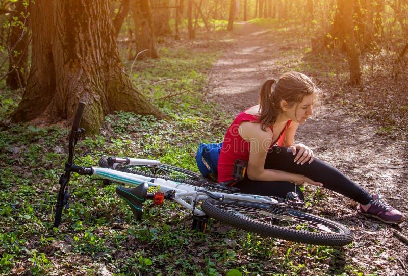 La mujer joven se cayó de la bicicleta fotografía de archivo libre de regalías