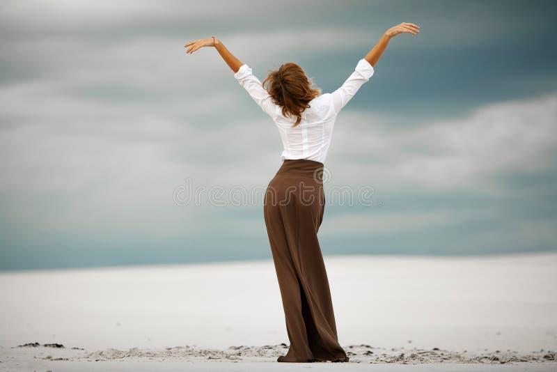 La mujer joven se coloca en la arena en desierto Visión posterior fotos de archivo libres de regalías