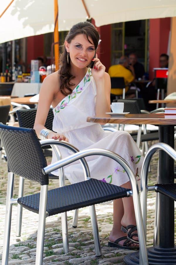 La mujer joven se está sentando en el café fotos de archivo