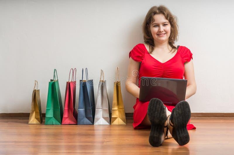 La mujer joven se está sentando en piso con el ordenador portátil y está haciendo compras en línea de hogar fotos de archivo libres de regalías