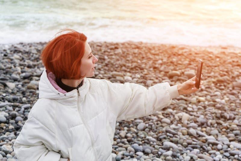 La mujer joven se fotografía en el teléfono en la costa contra el contexto de las ondas del mar en la puesta del sol imagen de archivo libre de regalías
