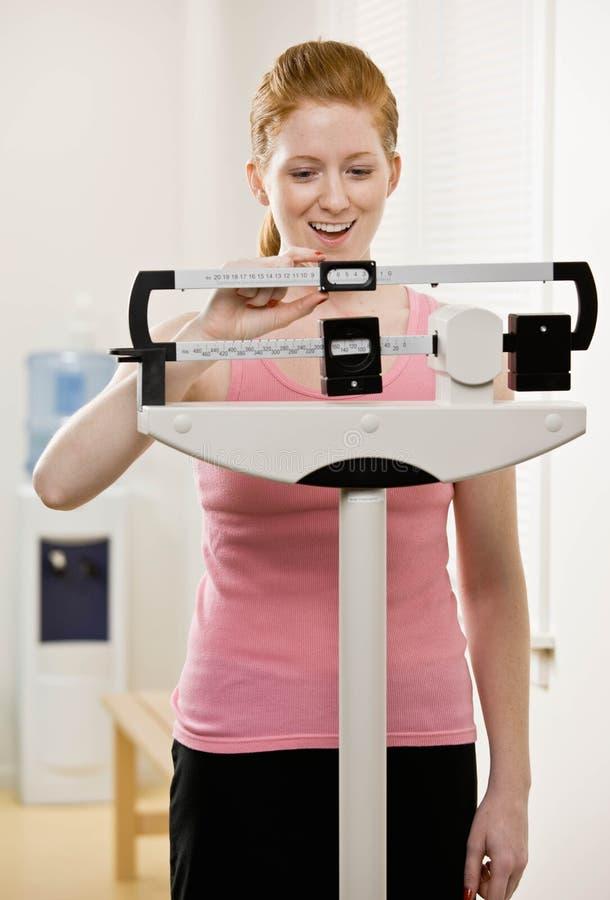La mujer joven se pesa en la gimnasia foto de archivo