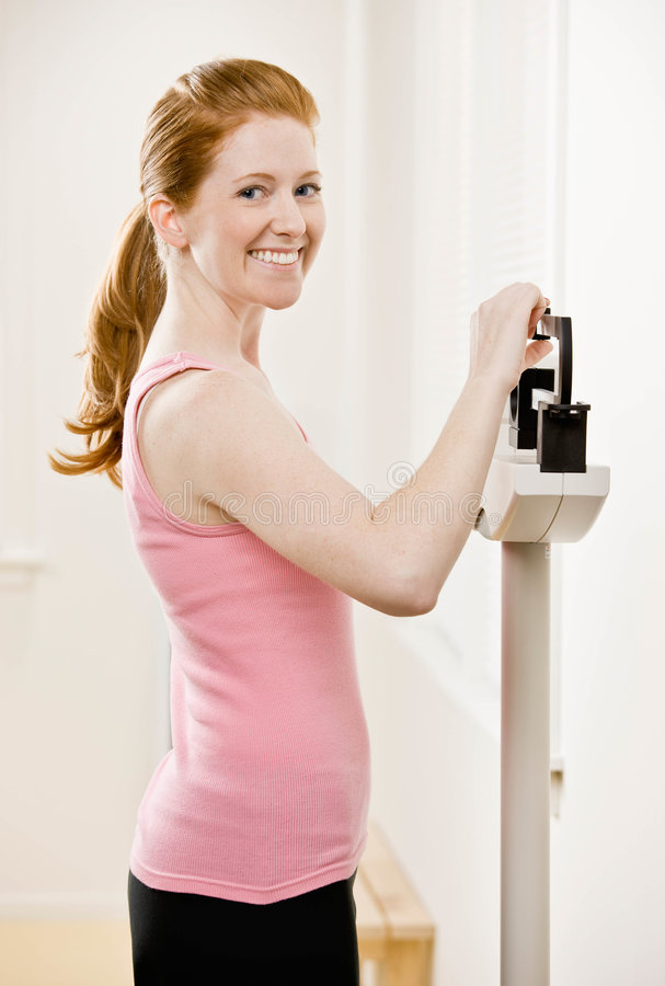 La mujer joven se pesa en la gimnasia imagenes de archivo