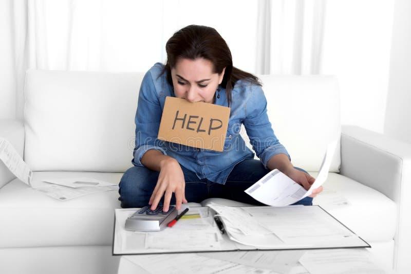 La mujer joven se preocupó en casa en considerar de la tensión desesperado en problemas financieros fotografía de archivo