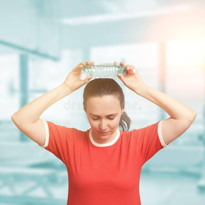 La mujer joven se refresca abajo después de entrenamiento con la botella de agua fría Ojos imagen de archivo libre de regalías