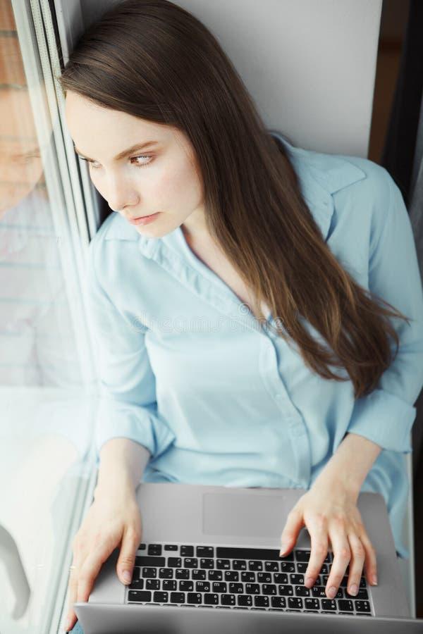 La mujer joven se sienta con aire y el ordenador portátil pensativos en revestimiento imágenes de archivo libres de regalías