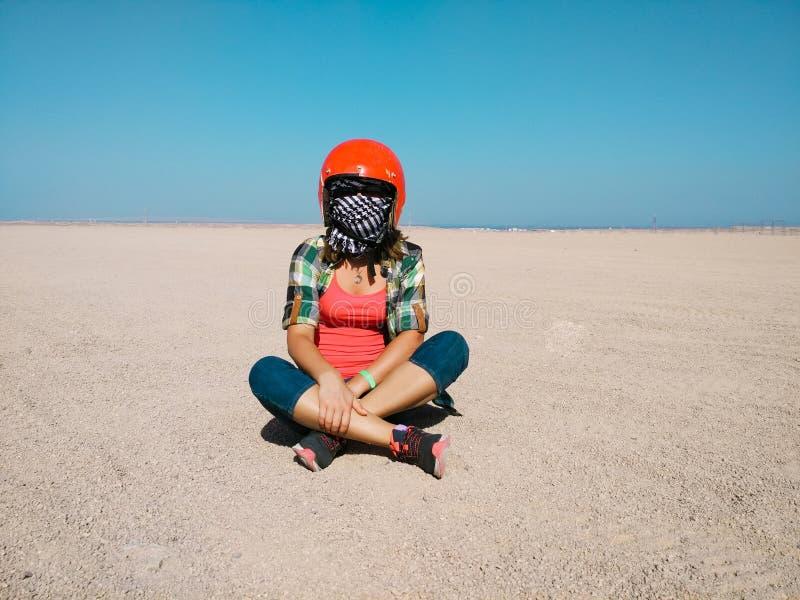 La mujer joven se sienta en el desierto que lleva un casco para el cochecillo imagen de archivo libre de regalías