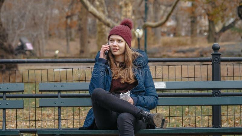 La mujer joven se sienta en un banco en el Central Park Nueva York foto de archivo libre de regalías
