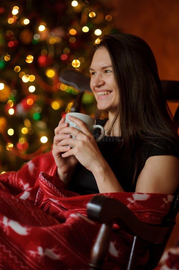 La mujer joven se sienta en una mecedora cerca del árbol de navidad fotografía de archivo