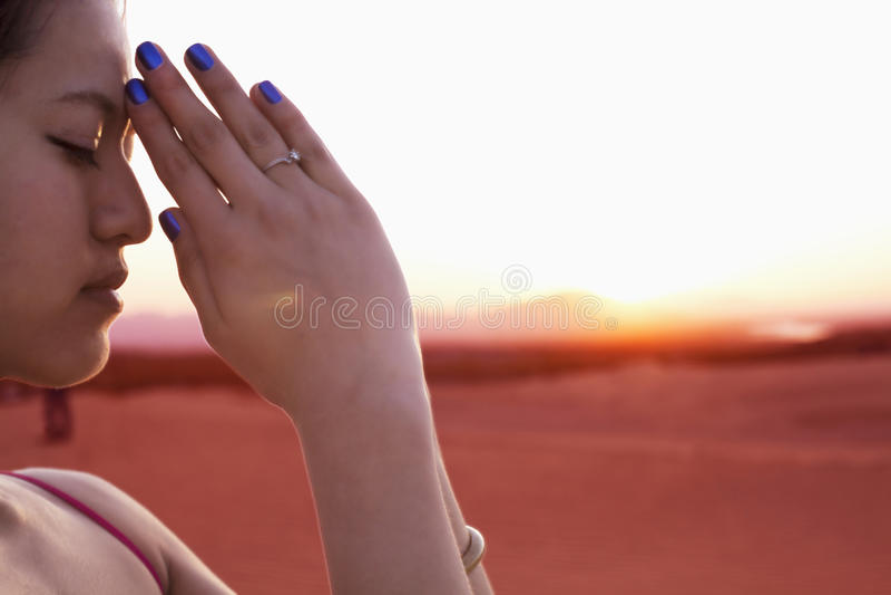 La mujer joven serena con los ojos se cerró y las manos junta en la actitud en el desierto en China, vista lateral del rezo fotos de archivo