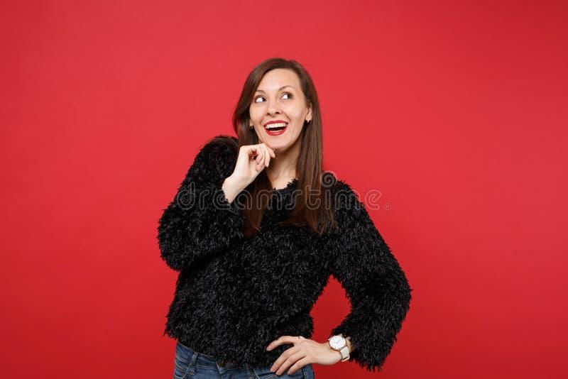 La mujer joven soñadora en el suéter negro de la piel que miraba para arriba, puso la mano apoya para arriba en la barbilla aisla imágenes de archivo libres de regalías