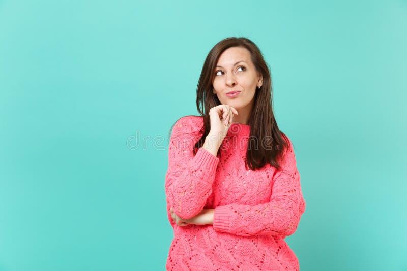 La mujer joven soñadora pensativa en el suéter rosado hecho punto que mira encima de la mano puesta apoya para arriba en la barbi foto de archivo libre de regalías
