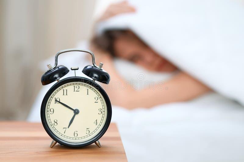 La mujer joven soñolienta debajo de la manta con su cabeza pone el ` t quiere despertar delante del primer del despertador Despie fotografía de archivo libre de regalías