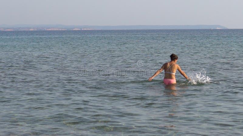 La mujer joven sola juega solamente en el mar fotografía de archivo libre de regalías
