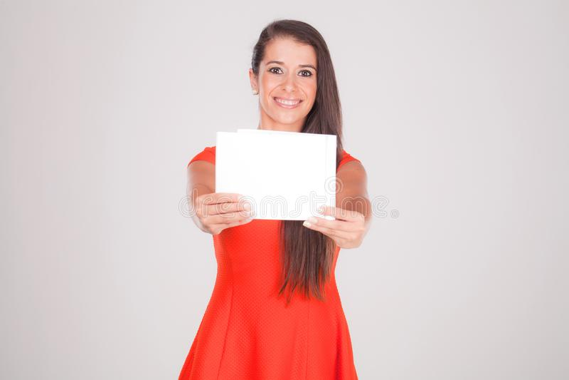 La mujer joven sonríe con un papel en blanco imagen de archivo libre de regalías