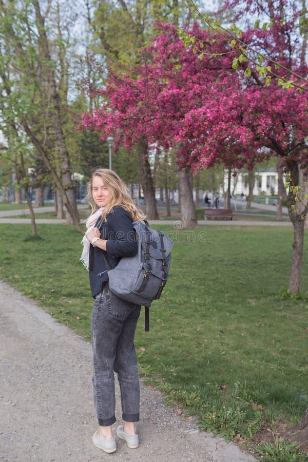 La mujer joven sonríe y camina a través del parque de la primavera fotografía de archivo libre de regalías