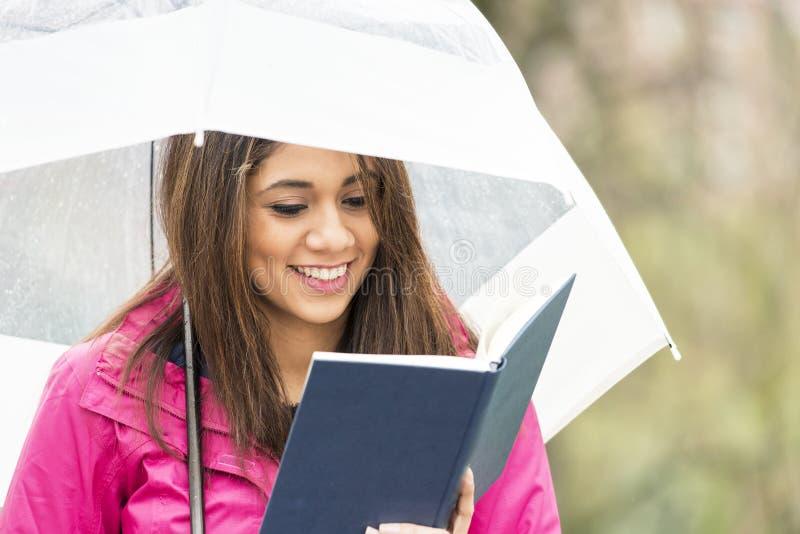 La mujer joven sonriente con el paraguas lee el libro en el parque imagen de archivo