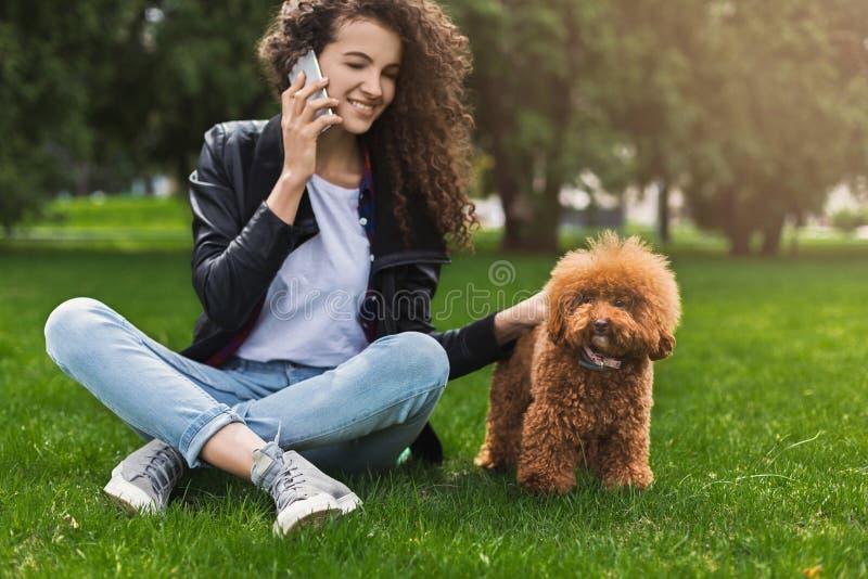 La mujer joven sonriente con el perro móvil y pequeño en la ciudad parquea imagen de archivo