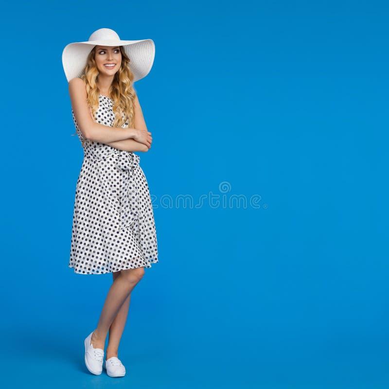 La mujer joven sonriente en vestido del verano, zapatillas de deporte y el sombrero blanco de Sun está mirando lejos imágenes de archivo libres de regalías
