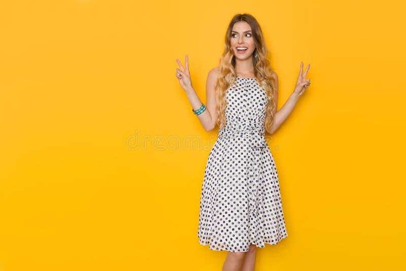 La mujer joven sonriente en vestido punteado verano está mostrando el signo de la paz fotos de archivo