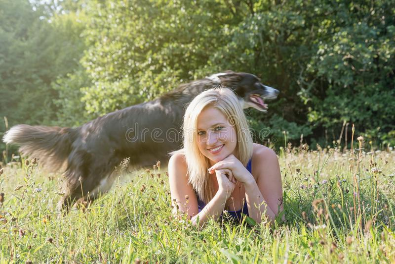 La mujer joven sonriente está mintiendo en la hierba mientras que su frontera Colli foto de archivo libre de regalías