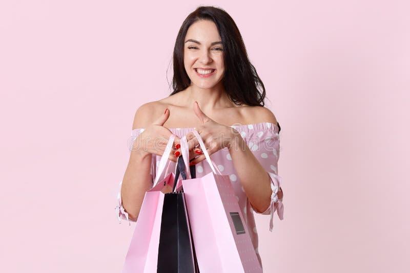La mujer joven sonriente feliz sostiene bolsos de compras, disfruta las nuevas compras, vestidas en vestido del lunar, hace compr fotos de archivo libres de regalías
