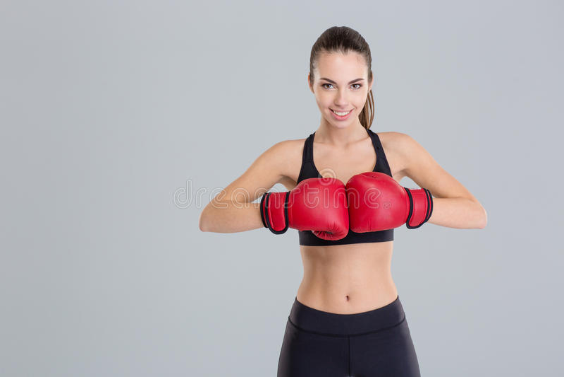 La mujer joven sonriente hermosa de la aptitud lleva guantes de boxeo rojos foto de archivo libre de regalías