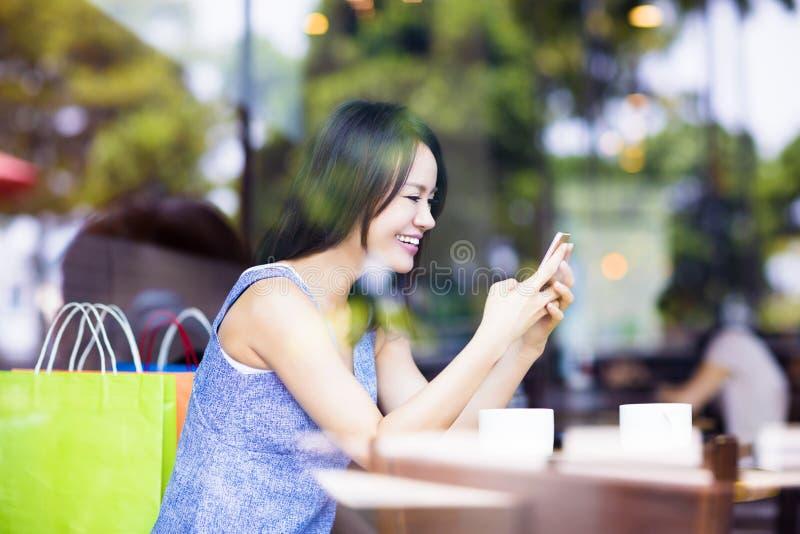 La mujer joven sonriente que mira el teléfono elegante en café hace compras fotos de archivo libres de regalías